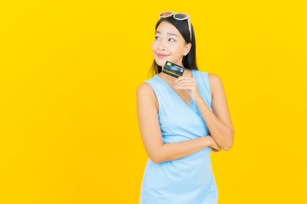 Sorriso di bella giovane donna asiatica del ritratto con carta di credito sulla parete di colore giallo