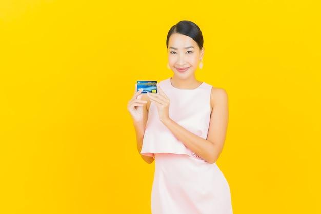 Sorriso di bella giovane donna asiatica del ritratto con carta di credito su giallo