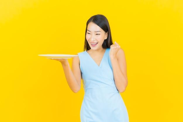 Sorriso della bella giovane donna asiatica del ritratto con il piatto vuoto del piatto sulla parete di colore giallo