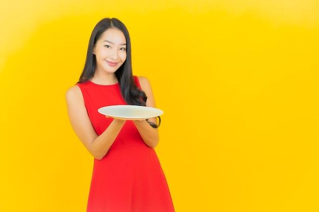 Sorriso della bella giovane donna asiatica del ritratto con il piatto vuoto del piatto sulla parete gialla