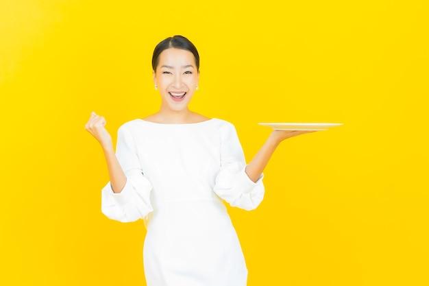 Ritratto bella giovane donna asiatica sorriso con piatto piatto vuoto su yellow