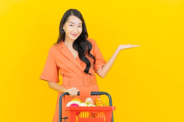 Sorriso della bella giovane donna asiatica del ritratto con il cestino della drogheria dal supermercato su colore giallo