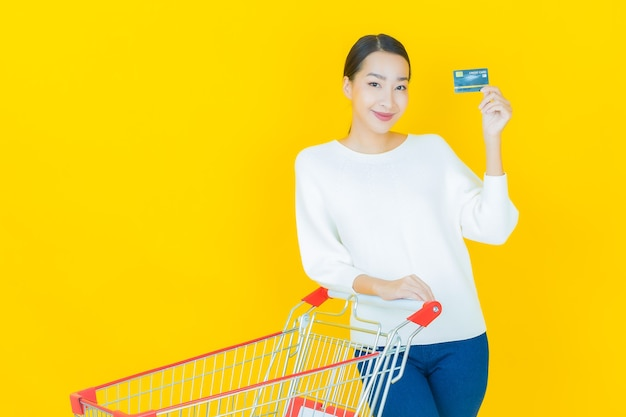 Ritratto bella giovane donna asiatica sorriso con cesto della spesa dal supermercato su yellow