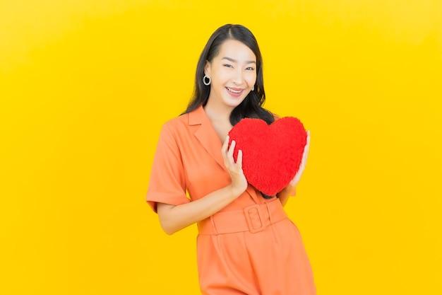 Sorriso della bella giovane donna asiatica del ritratto con la forma del cuscino del cuore su colore giallo