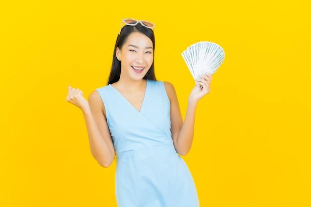 Ritratto bella giovane donna asiatica sorriso con un sacco di soldi e contanti sulla parete di colore giallo