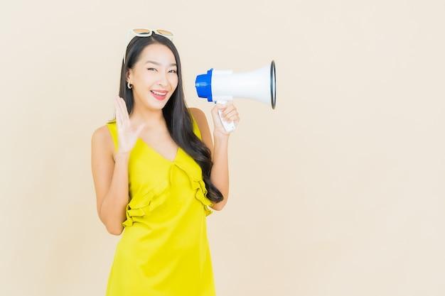 Sorriso della bella giovane donna asiatica del ritratto con il megafono sulla parete di colore