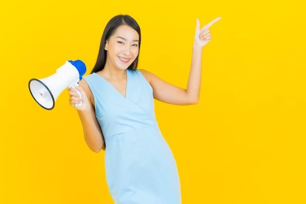 Sorriso di bella giovane donna asiatica del ritratto con il megafono sulla parete di colore giallo
