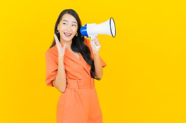 Sorriso della bella giovane donna asiatica del ritratto con il megafono su colore giallo