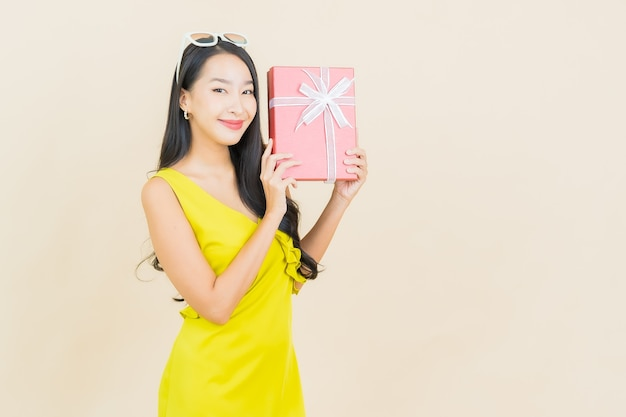 Sorriso della bella giovane donna asiatica del ritratto con il contenitore di regalo rosso sulla parete di colore