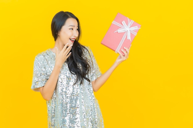 Sorriso della bella giovane donna asiatica del ritratto con il contenitore di regalo rosso su giallo