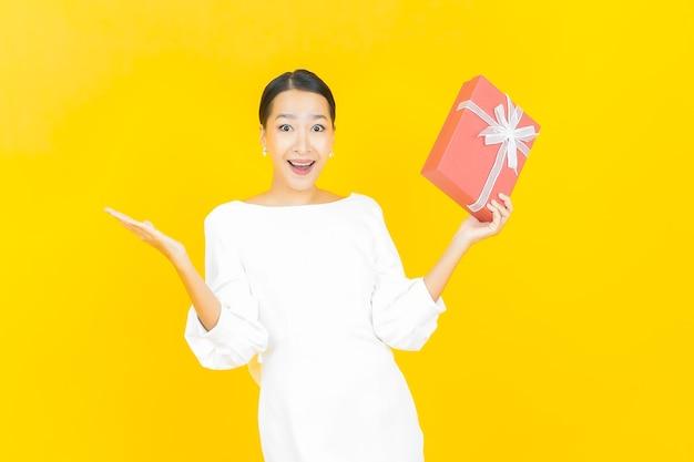 Ritratto bella giovane donna asiatica sorriso con confezione regalo rossa su giallo