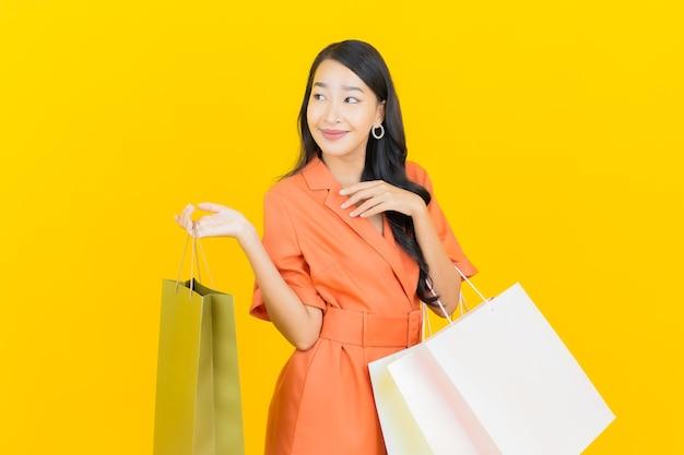 Sorriso della bella giovane donna asiatica del ritratto con il sacchetto della spesa su colore giallo