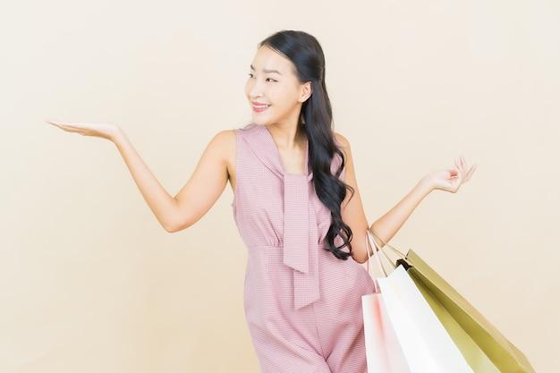 Sorriso della bella giovane donna asiatica del ritratto con il sacchetto della spesa