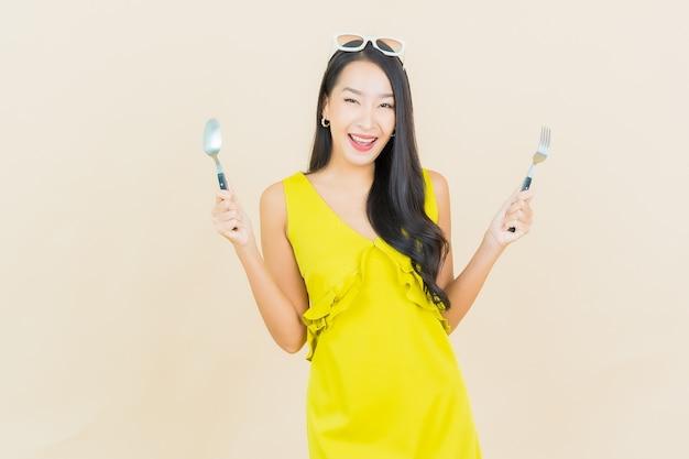Ritratto bella giovane donna asiatica sorriso con cucchiaio e forchetta sulla parete di colore
