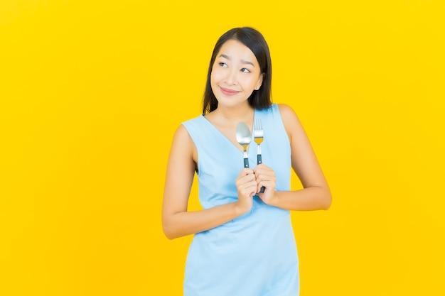Sorriso di bella giovane donna asiatica del ritratto con cucchiaio e forchetta sulla parete di colore giallo