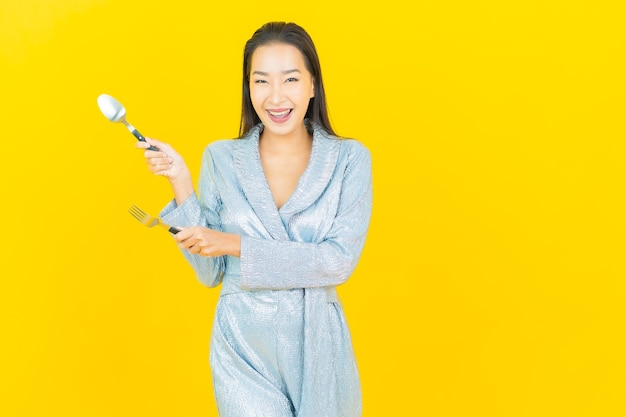 Sorriso di bella giovane donna asiatica del ritratto con cucchiaio e forchetta sulla parete gialla