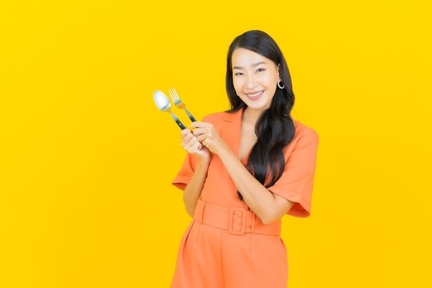 Sorriso di bella giovane donna asiatica del ritratto con cucchiaio e forchetta su colore giallo