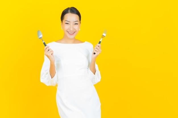 Ritratto bella giovane donna asiatica sorriso con cucchiaio e forchetta su yellow