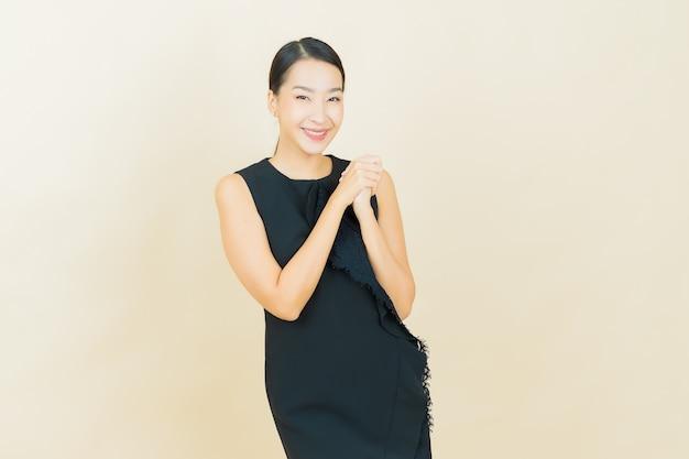 La bella giovane donna asiatica del ritratto sorride sulla parete di colore