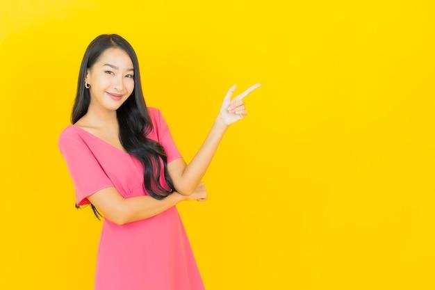 Ritratto di bella giovane donna asiatica sorride in abito rosa sulla parete gialla