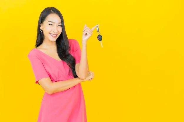 La bella giovane donna asiatica del ritratto sorride con la chiave dell'automobile sulla parete gialla