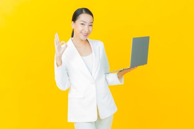 La bella giovane donna asiatica del ritratto sorride con il computer portatile del computer sulla parete isolata