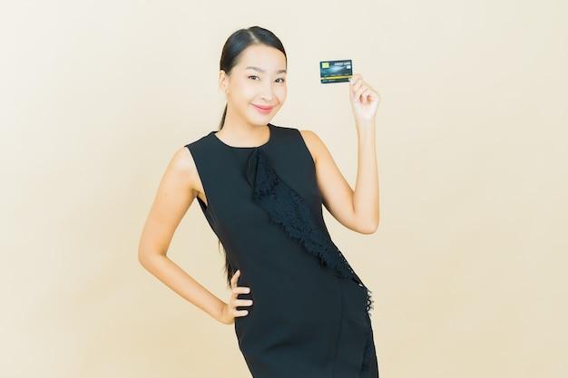 La bella giovane donna asiatica del ritratto sorride con la carta di credito sulla parete di colore