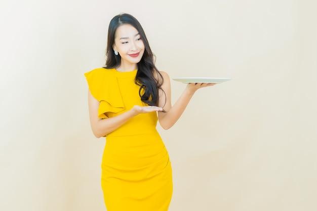 La bella giovane donna asiatica del ritratto sorride con il piatto vuoto del piatto sulla parete beige