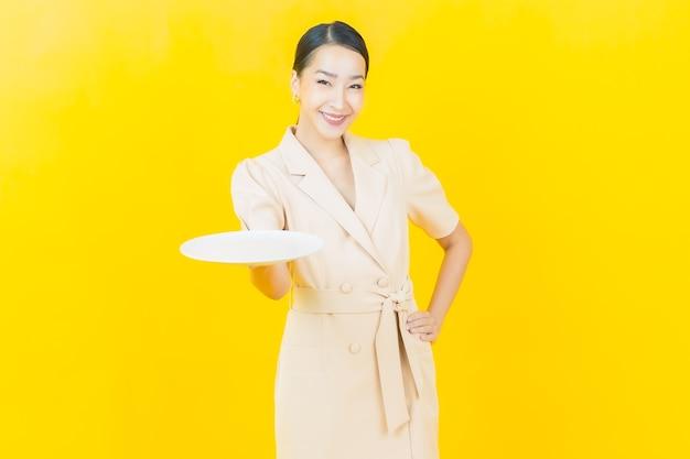 La bella giovane donna asiatica del ritratto sorride con il piatto vuoto del piatto sulla parete di colore