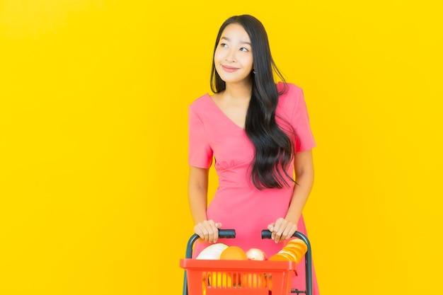 La bella giovane donna asiatica del ritratto sorride con il cestino della drogheria dal supermercato sulla parete gialla