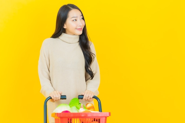 La bella giovane donna asiatica del ritratto sorride con il cestino della spesa dal supermercato sulla parete gialla