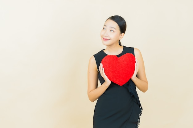La bella giovane donna asiatica del ritratto sorride con la forma del cuscino del cuore sulla parete di colore