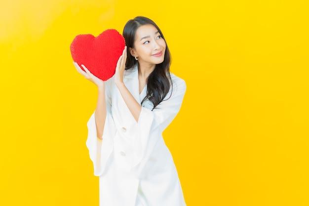 Il ritratto di bella giovane donna asiatica sorride con la forma del cuscino del cuore sulla parete gialla