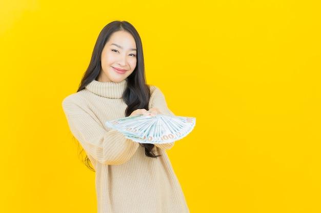 La bella giovane donna asiatica del ritratto sorride con molti contanti e soldi sulla parete gialla