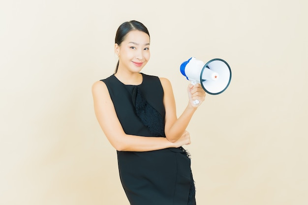 La bella giovane donna asiatica del ritratto sorride con il megafono sulla parete di colore