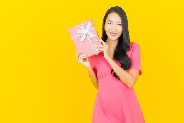 La bella giovane donna asiatica del ritratto sorride con il contenitore di regalo rosso sulla parete gialla