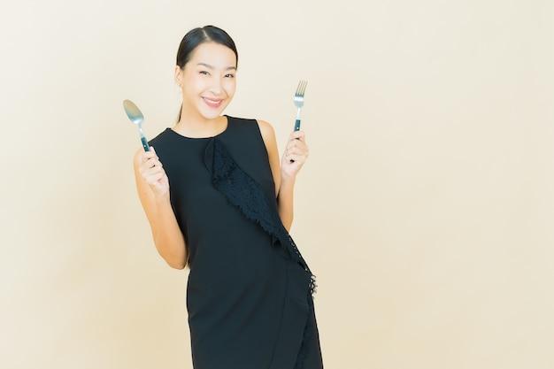 La bella giovane donna asiatica del ritratto sorride con il cucchiaio e la forchetta sulla parete di colore