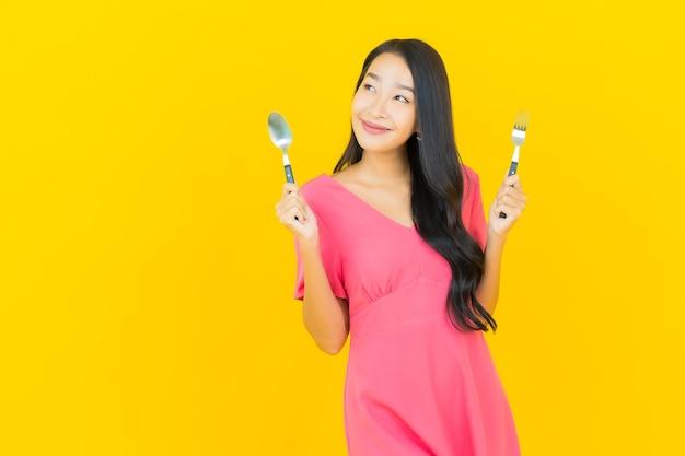 La bella giovane donna asiatica del ritratto sorride con il cucchiaio e la forchetta sulla parete gialla