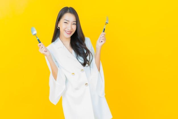 Il ritratto di bella giovane donna asiatica sorride con il cucchiaio e la forchetta sulla parete gialla