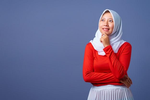 Ritratto di una giovane e bella donna asiatica che pensa di trovare idee con una faccia sorridente