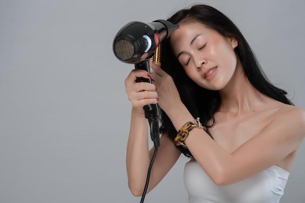 Ritratto di bella giovane donna asiatica utilizza asciugacapelli su grigio.