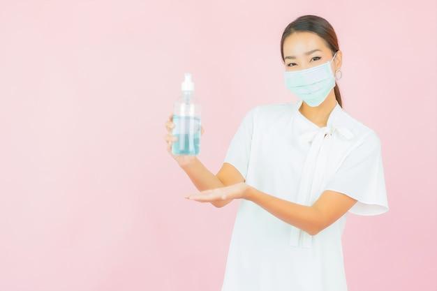 La bella giovane donna asiatica del ritratto indossa la maschera per proteggere covid19 sulla parete rosa