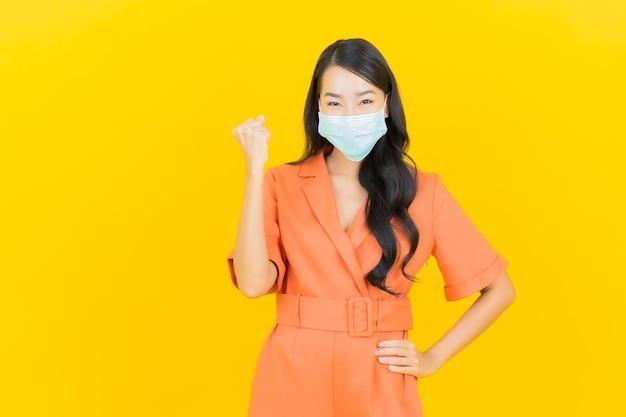 La bella giovane donna asiatica del ritratto indossa la maschera per la protezione covid19 su giallo