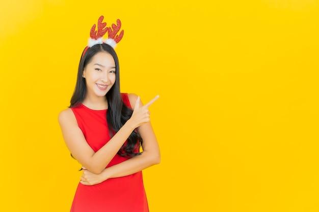 La bella giovane donna asiatica del ritratto porta il cappello o la fascia per capelli della santa sulla parete gialla