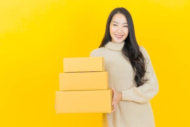 Ritratto bella giovane donna asiatica con scatola pronta per la spedizione su parete gialla