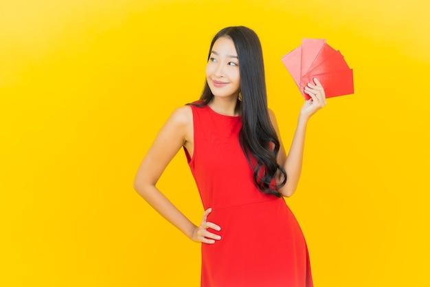 Bella giovane donna asiatica del ritratto con la busta rossa del nuovo anno cinese sulla parete gialla