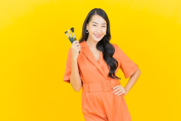 La bella giovane donna asiatica del ritratto con cosmetico compone la spazzola su colore giallo