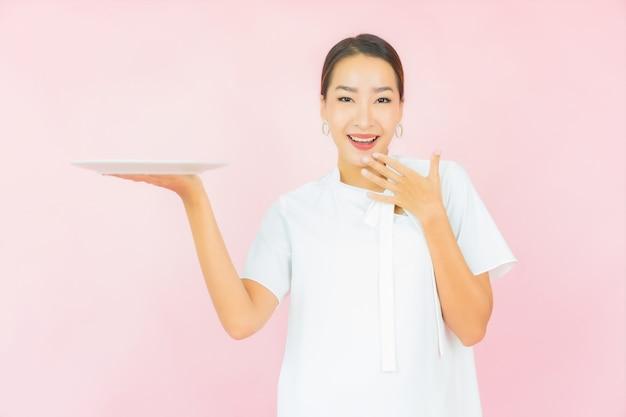 Bella giovane donna asiatica del ritratto con il piatto vuoto del piatto sul colore rosa
