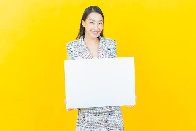 Bella giovane donna asiatica del ritratto con il tabellone per le affissioni bianco vuoto sulla parete di colore
