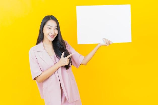 Bella giovane donna asiatica del ritratto con il tabellone per le affissioni bianco vuoto sulla parete gialla